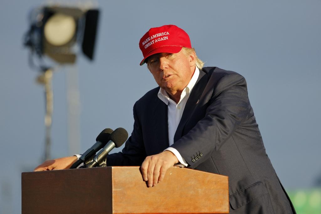 SAN PEDRO, CA - SEPTEMBER 15, 2015: Donald Trump, 2016 Republican presidential candidate, speaks during a rally aboard the Battleship USS Iowa in San Pedro, Los Angeles, California while wearing a red baseball hat that says campaign slogan