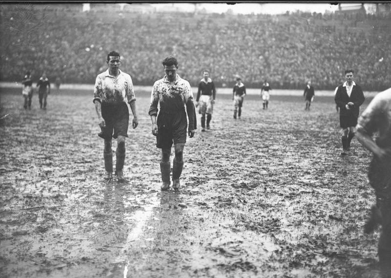 27th February 1937:  Two Preston North End players leave the pitch at half-time covered in mud, during a match against Charlton Athletic at 'The Valley'.  (Photo by J. A. Hampton/Topical Press Agency/Getty Images)